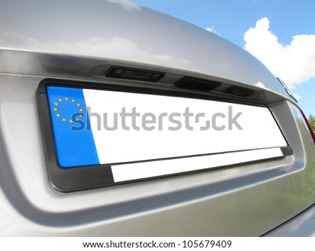 Silver car back view with empty white  number plate on  blue sky with clouds background - stock photo