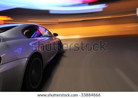 Silver car moving at speed under neon lighting