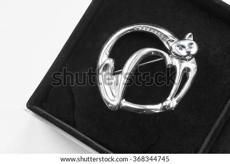 Silver cat brooch in black velvet box closeup - stock photo