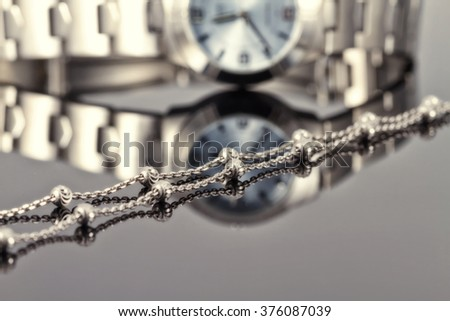 Silver chain ladies watch chrome-plated steel lying on the reflecting surface - stock photo