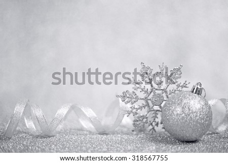 Silver christmas balls and snowflakes on shining glitter background with copy space - stock photo