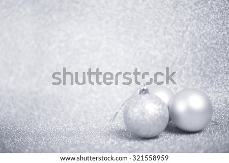 Silver christmas balls on shiny glitter background close-up