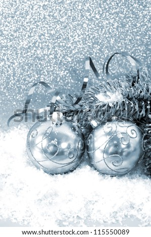 silver christmas balls with christmas tree branch in snow - stock photo