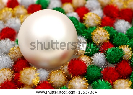 Silver Christmas bauble resting on colorful puff ball decorations - stock photo