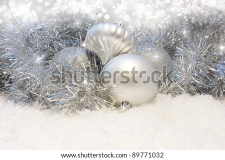 Silver Christmas baubles nestled in tinsel and snow
