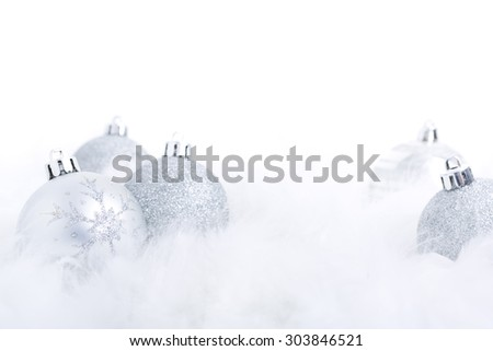 Silver Christmas baubles on a soft feathery surface with a white background. - stock photo