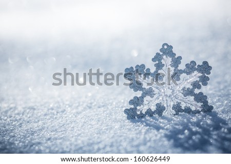 Silver Christmas decoration. Beautiful snowflake on real snow outdoors. Winter holidays concept - stock photo