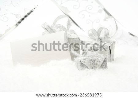 Silver christmas decoration, gifts with ribbon with wishes card on snow white background - stock photo