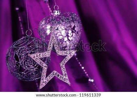 Silver christmas decoration on purple fabric background - stock photo