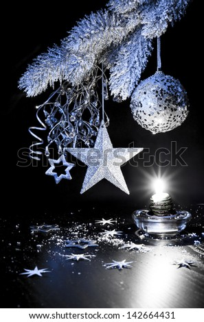 Silver Christmas decorations, candle on a table - stock photo