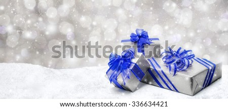 Silver Christmas or birthday gift boxes with red bows in snow, with snowy night background, panorama format