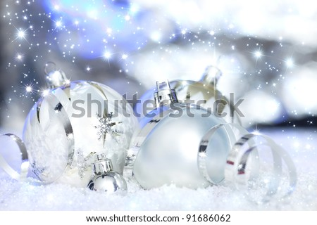 silver christmas ornamnets in snow before reflective background - stock photo