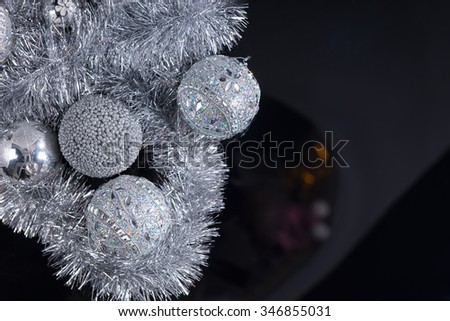 Silver Christmas still life background with decorative baubles entwined in tinsel on a black background with copyspace for your seasonal message