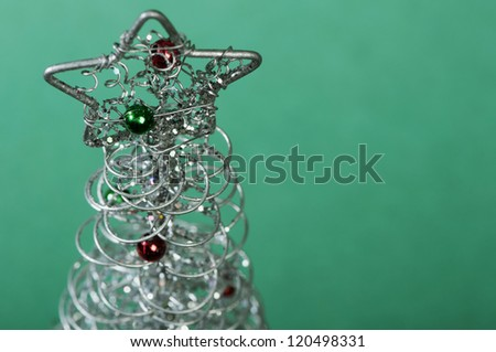 Silver Christmas tree with ornaments. Green Background - stock photo