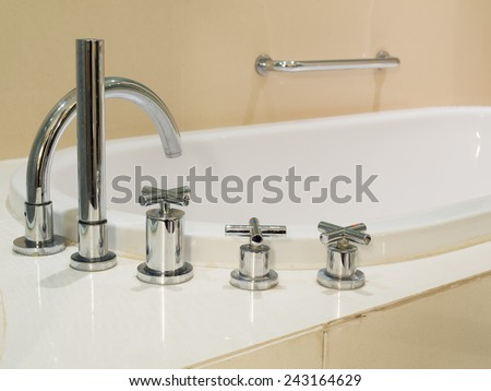 Silver chrome tap with bathtub, modern bathroom - stock photo