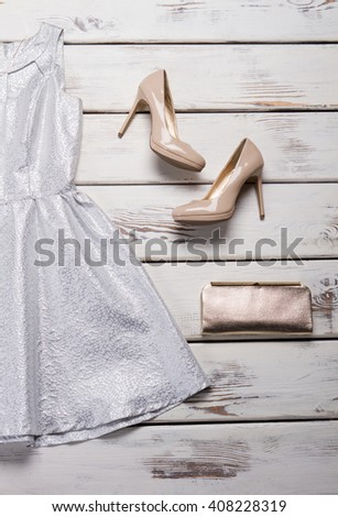 Silver clutch bag and footwear. White table with clutch bag. Woman's trendy silver handbag. New evening shoes in stock. - stock photo