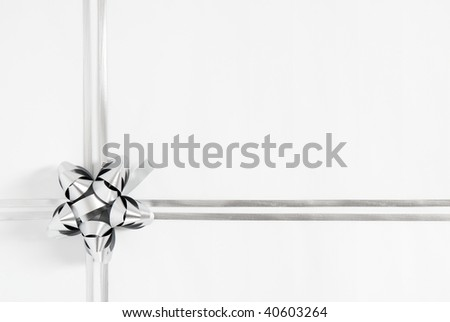 Silver cockade and strings on white paper background