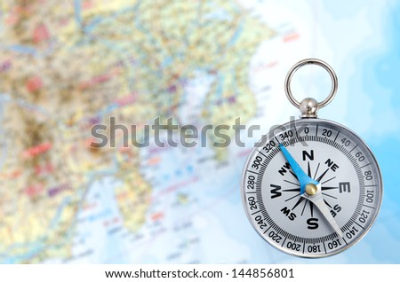Silver Compass isolated on Map background. - stock photo