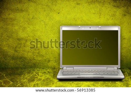 silver computer on green and dirty background - stock photo