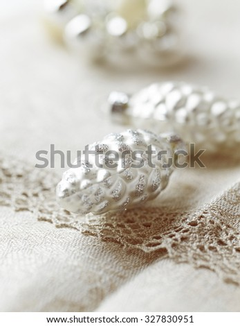 Silver cone-shaped Christmas ornaments on a linen table cloth - stock photo