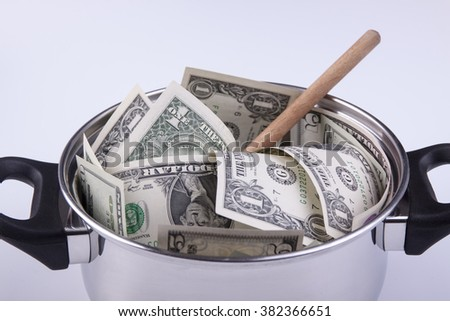 Silver cooking pot full of dollar banknotes with wooden spoon