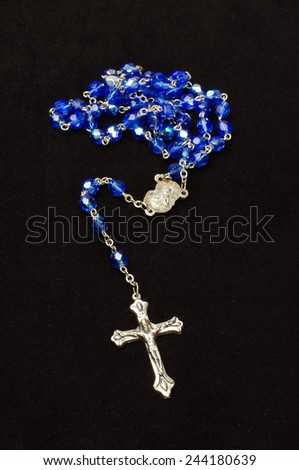 Silver cross crucifix and blue glass rosary isolated