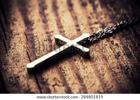 Silver cross on a wood background close up image - stock photo
