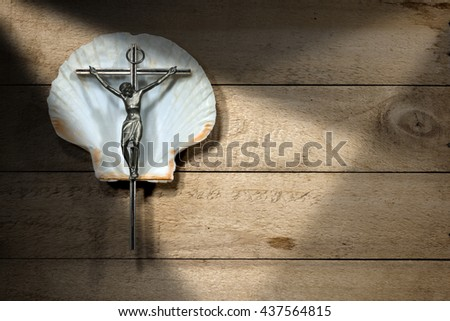 Silver crucifix on a white scallop seashell on a wooden background. Symbol of Christian pilgrimage - stock photo