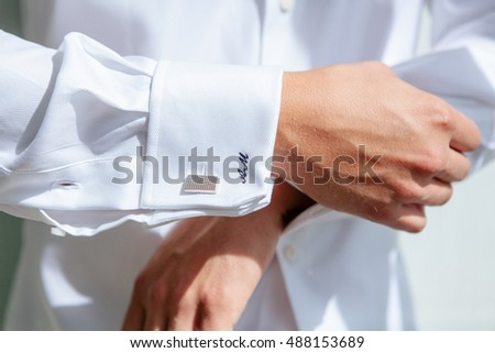 Silver cufflinks on the white shirt of the groom