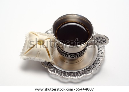 Silver cup of coffee with cake is on the white background