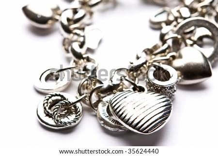 Silver designer costume jewelery in macro on white background - stock photo