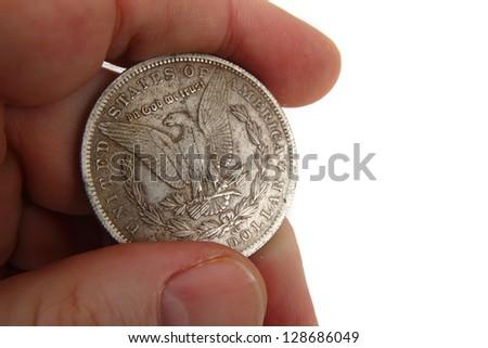 silver dollar coin in human hand - stock photo