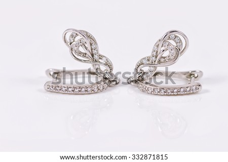 silver earrings in the shape of a horseshoe with cubic Zirconia in white acrylic