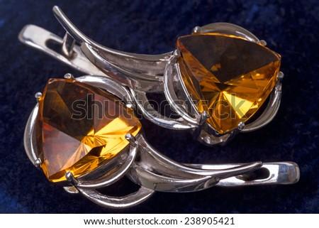 Silver earrings with citrine on a dark blue velvet - stock photo