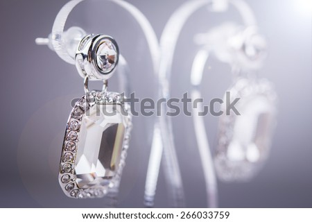 Silver earrings with diamond. Isolated on grey. Lens flare - stock photo