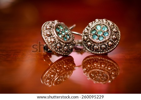 Silver earrings with green stones on a varnished wooden background - stock photo