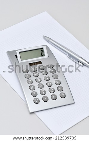 silver electronic calculator, notepad and pen - stock photo