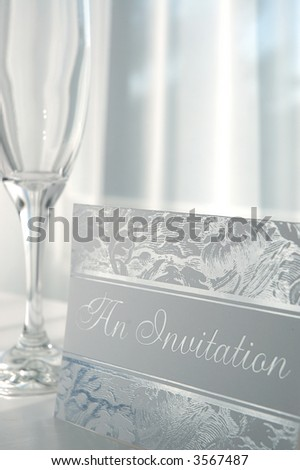 silver embossed invitation card and champagne glass - stock photo
