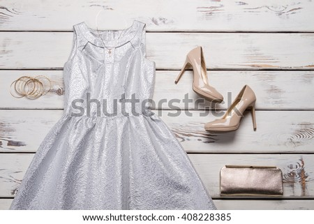 Silver evening dress with accessories. Evening outfit on wooden shelf. Girl's apparel and heel shoes. Fashionable clothing sold at discount. - stock photo