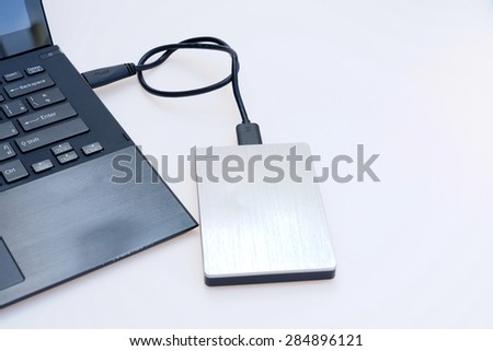 Silver external hard disk connect to computer notebook on white. - stock photo