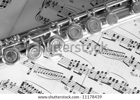 Silver flute resting on complicated sheet music - stock photo