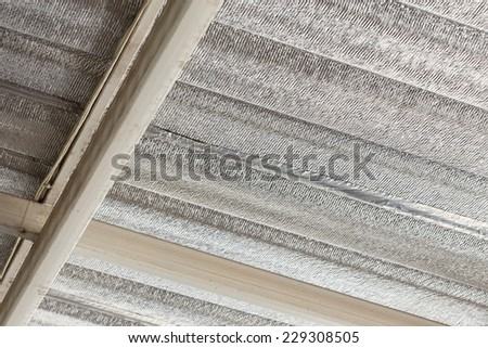 silver foil insulation on ceiling roof house - stock photo