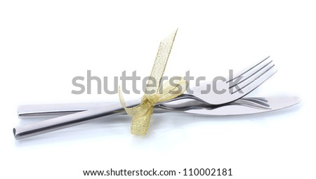 Silver fork and knife tied with ribbon isolated on white - stock photo