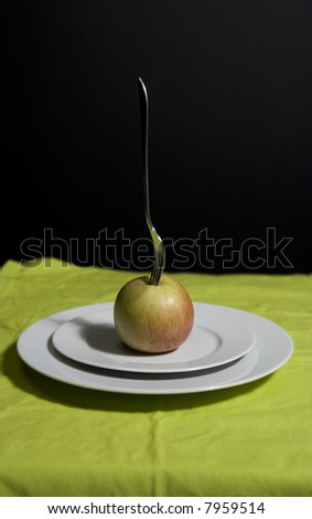 silver fork in apple on plate with green table cloth