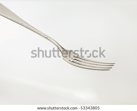 Silver fork in front of a light background