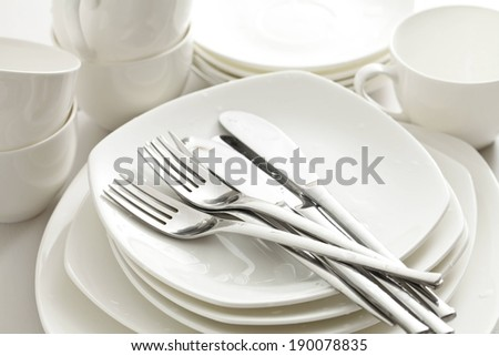 Silver forks and knives rest on a stack of plates and dishes, with white mugs behind. - stock photo
