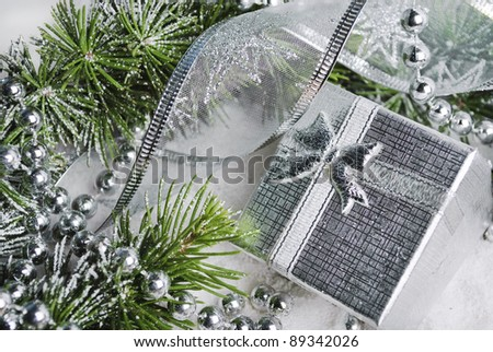 Silver gift box and christmas decoration in snow - stock photo