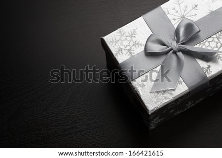 Silver gift box on dark background with copyspace