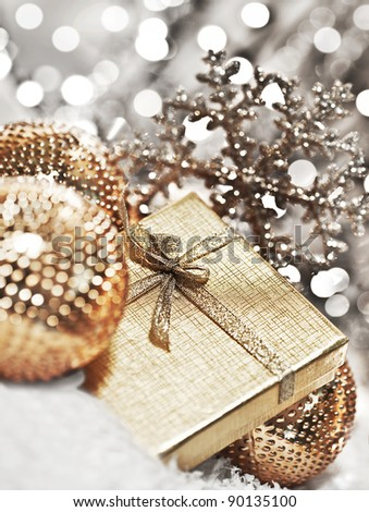 Silver gift box with baubles decorations, Christmas tree ornament for winter holidays, present with abstract bokeh shiny glowing blur lights background - stock photo