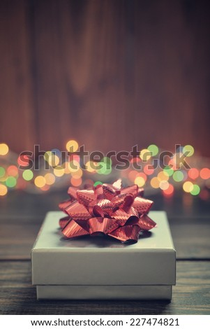 Silver gift box with red bow over wooden background - stock photo